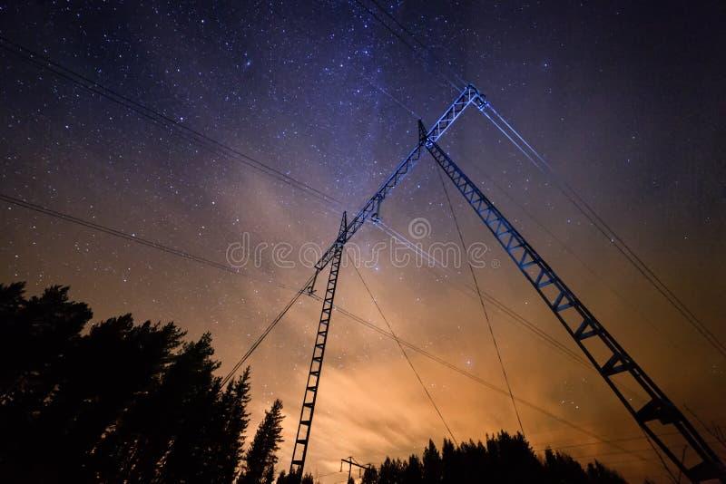 输电线在与满天星斗的天空的晚上 免版税库存照片