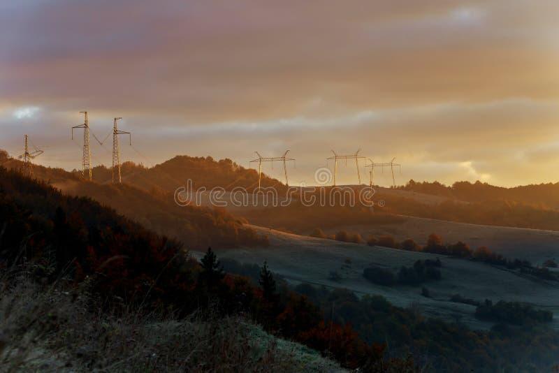 输电线塔在黎明前薄雾的在郊外 免版税库存图片