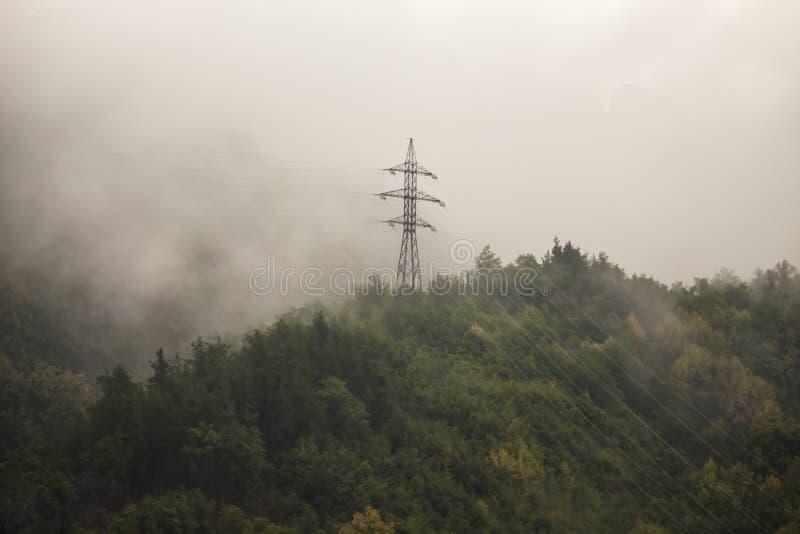 输电线是高在雾的山 免版税库存图片