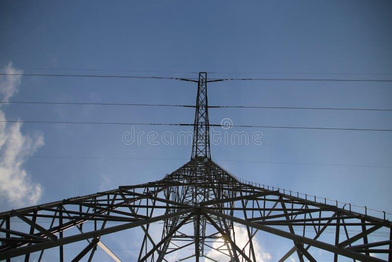 输电线的金属塔在天空蔚蓝和太阳与从下面看透视的白色云彩 库存照片