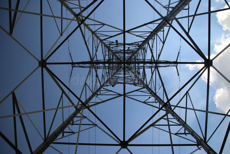 输电线的金属塔在天空蔚蓝和太阳与从下面看透视的白色云彩 免版税库存照片