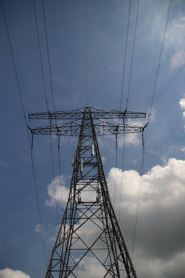 输电线的金属塔在天空蔚蓝和太阳与白色云彩 免版税库存图片