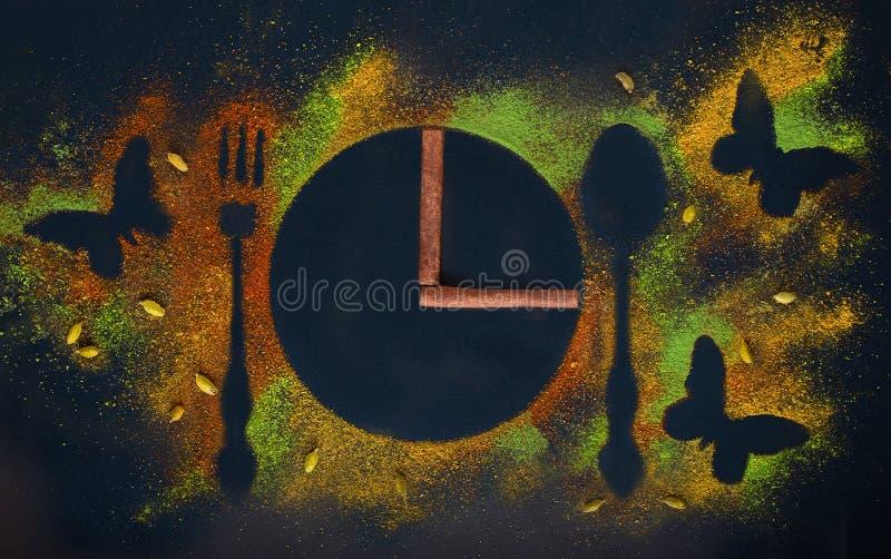 辣卡片由辣的香料、蝴蝶和时钟表盘制成与桂香箭头在豆蔻果实、姜黄、辣椒粉和辣椒 图库摄影