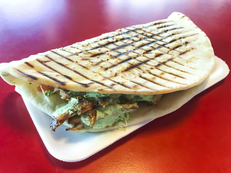 辣土耳其doner kebab充满烤肉、新鲜的沙拉和蒜酱油在敬酒的玉米粉薄烙饼 免版税图库摄影