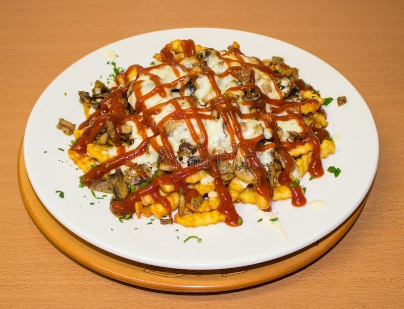 辣快餐:炸薯条用切达干酪、辣椒和鸡内圆角,在板材的特写镜头调味汁 背景 库存照片