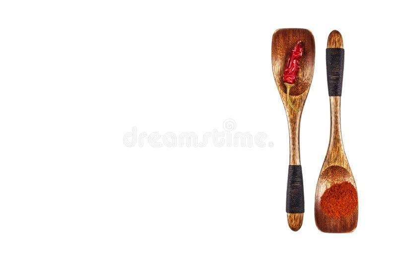 辣椒粉和新鲜的辣椒在一把木匙子 Powdered烘干了红辣椒,与木匙子的粉末辣椒粉 查出在白色 库存图片