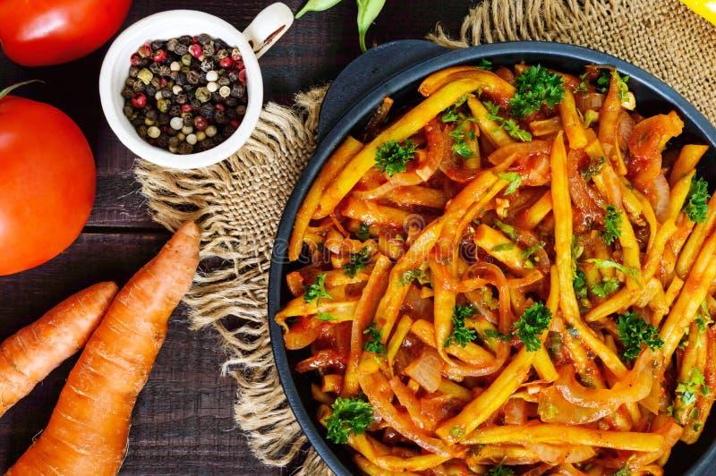 辣青豆炖了用葱,在西红柿酱的红萝卜 服务在黑暗的木背景的铸铁煎锅 免版税库存照片