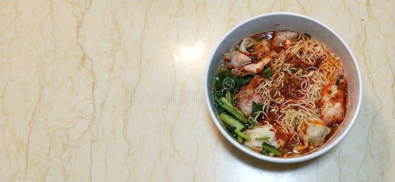 辣面条用饺子和烤红色猪肉 免版税库存照片