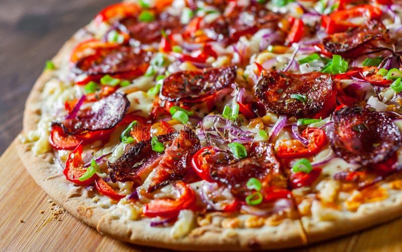辣香肠烘饼用无盐干酪乳酪,蒜味咸腊肠,西红柿酱,胡椒,葱,加香料 在木桌上的意大利薄饼 免版税库存照片