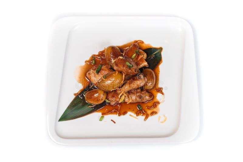 辣鸡用在竹叶子的土豆在被隔绝的白色背景的一块白色板材 库存图片