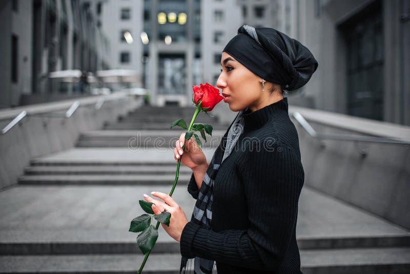 边在手上射击了在步的年轻阿拉伯妇女立场并且拿着红色玫瑰 她嗅到它 模型佩带黑hijab 免版税图库摄影