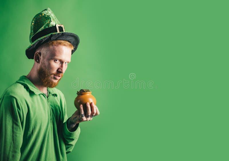 边界日pattys st 帕特里克斯天金壶和三叶草 圣帕特里克节妖精党的红色头发人在绿色 免版税库存图片