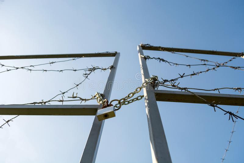 边界的门是与铁丝网的锁着和创伤 免版税库存照片