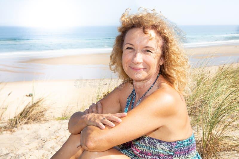 边缘沙丘海滩的微笑的退休的资深白肤金发的妇女在夏天 免版税库存照片