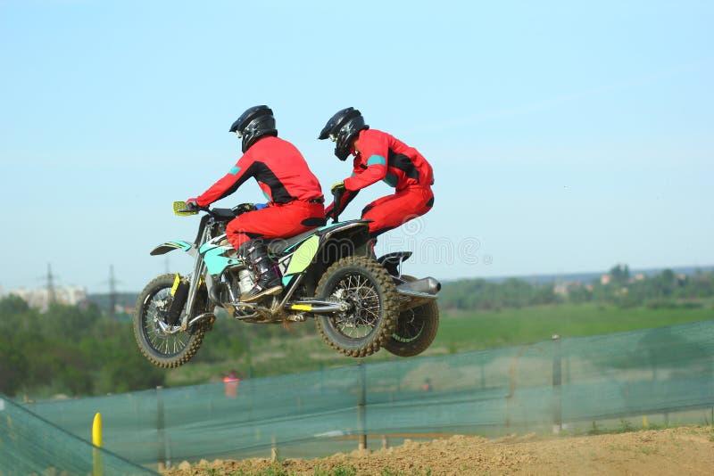 边车跳跃在天空中的摩托车越野赛运动员 图库摄影