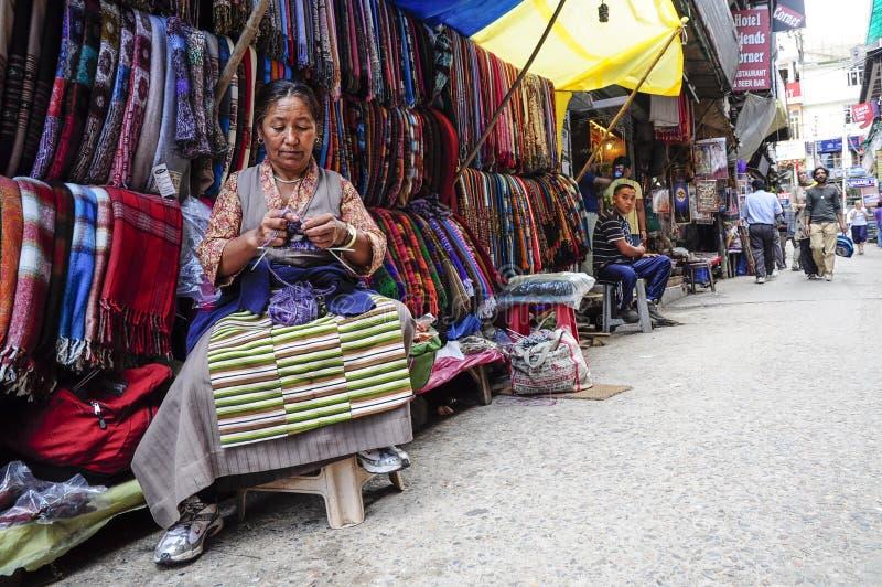 达兰萨拉,印度, 2010年9月8日:老印地安妇女编织在她的在一个地方街市上的商店前面的,达兰萨拉,印度 免版税库存照片