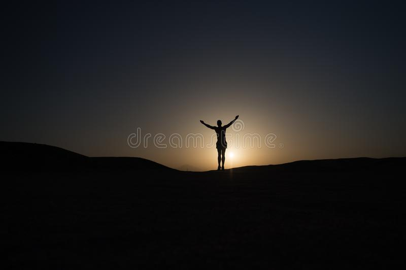 达到主要目标 剪影人立场骄傲在日落天空背景前面 未来成功取决于您的努力 免版税库存图片