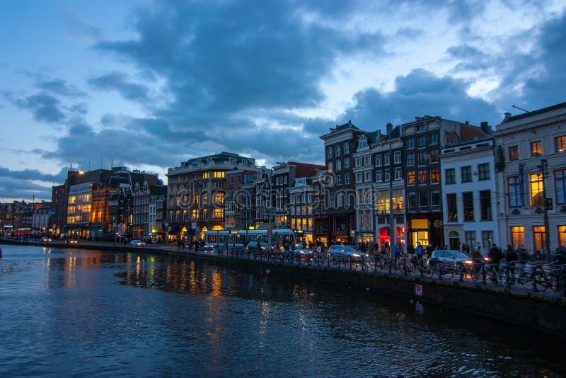 达姆拉克大街的传统运河房子黄昏的在阿姆斯特丹 库存图片