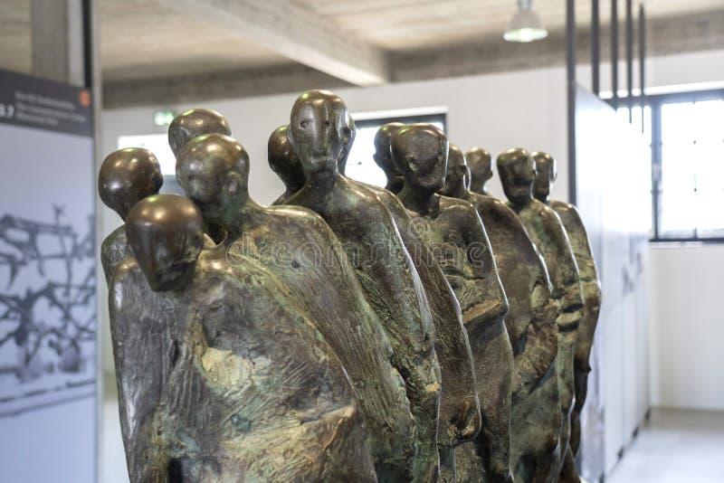 达豪,德语:2019年4月2日-囚犯和铁丝网篱芭被憔悴的身体启发的达豪纪念雕塑  dachau 免版税库存图片
