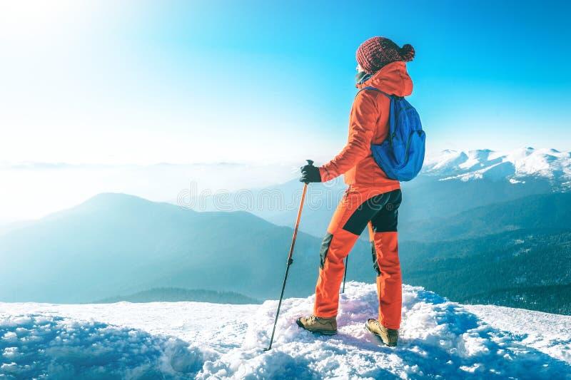 迁徙在一座多雪的山的雪的远足者愉快的妇女在wi 图库摄影