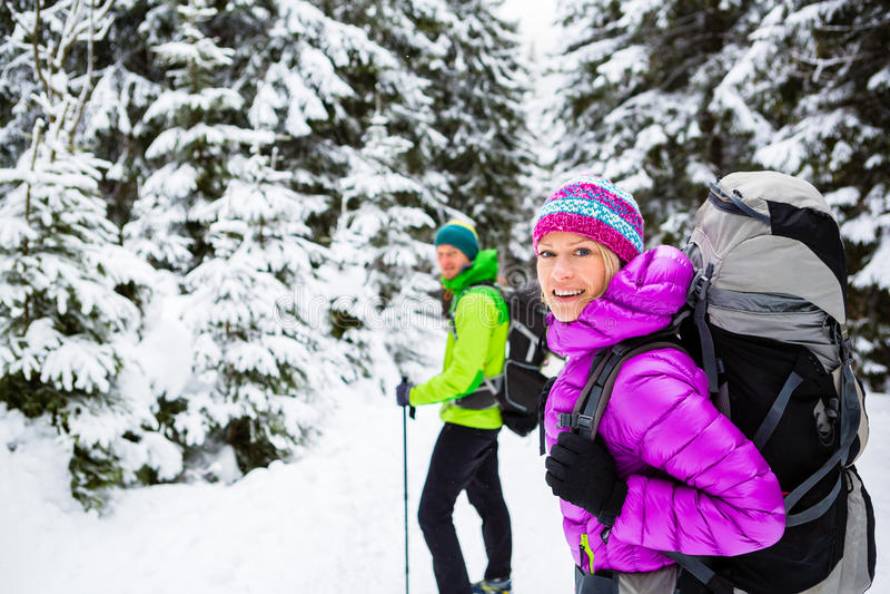 迁徙在冬天森林的夫妇远足者 免版税图库摄影