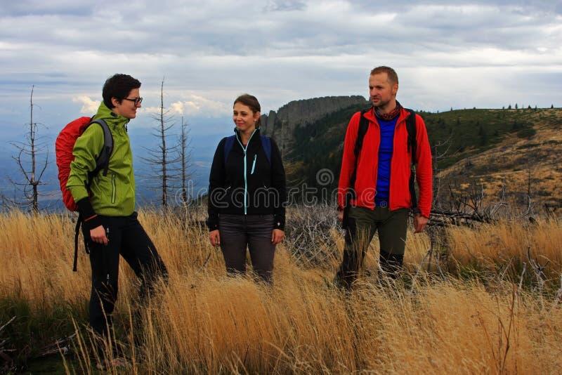迁徙在山的三个朋友 免版税库存照片
