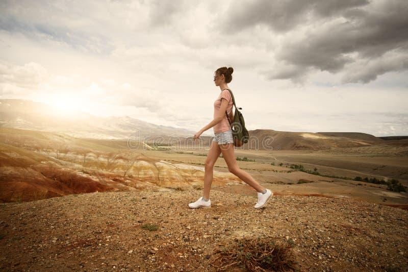 迁徙在山的妇女背包徒步旅行者 免版税库存照片