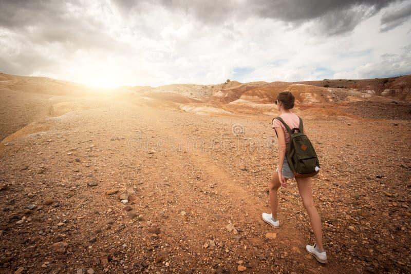 迁徙在山的妇女背包徒步旅行者 免版税库存图片