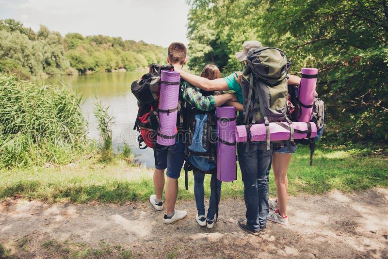 迁徙,野营,和谐,和平概念 朋友两对夫妇背面图结合在湖的长凳的,看是 图库摄影