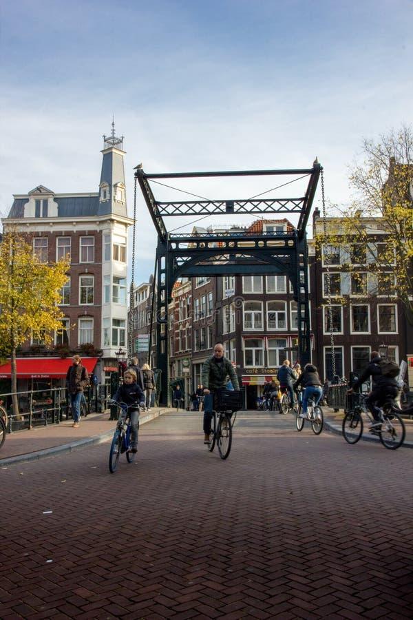 过一座桥梁的骑自行车者在阿姆斯特丹 免版税图库摄影