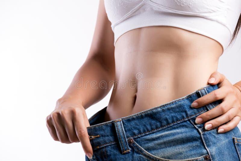 过大的蓝色牛仔裤的年轻亭亭玉立的妇女 穿太大裤子的适合妇女 医疗保健和妇女饮食减少的生活方式概念 免版税图库摄影