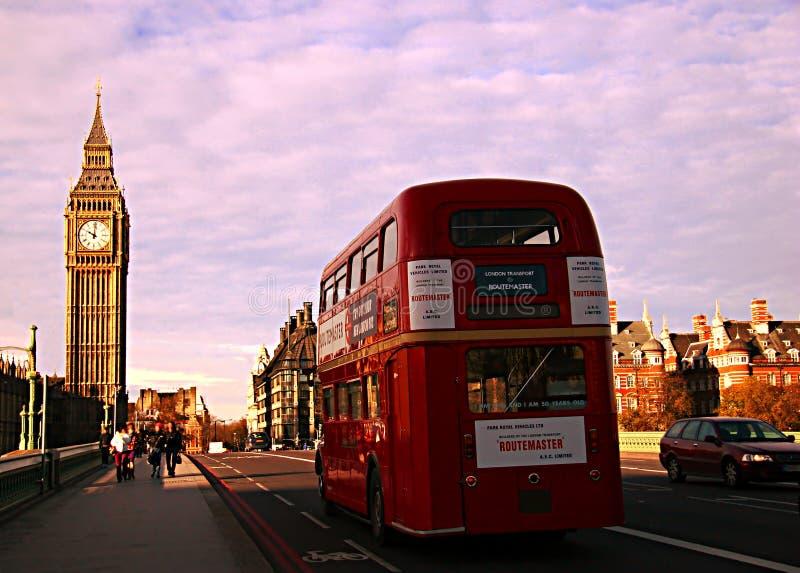 过威斯敏斯特桥梁,在direc的典型的伦敦红色公共汽车 库存照片