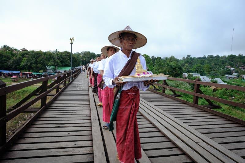 从过星期一桥梁的星期一村庄的人们 横渡khao laem人工湖的木桥 免版税库存图片