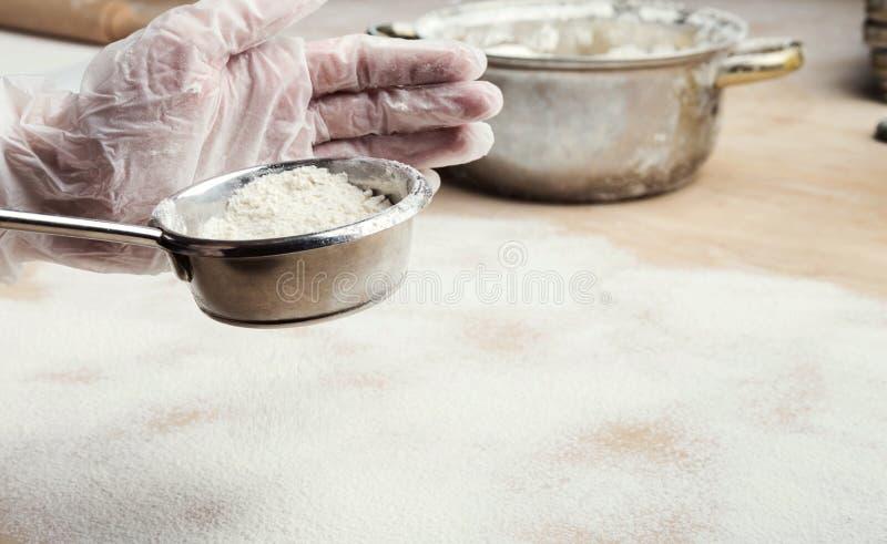 过滤从筛子的男性手面粉在木厨房用桌上 库存照片