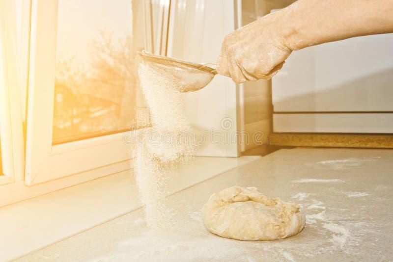 过滤面粉的女性手通过在碗特写镜头拷贝空间的手工面粉筛子 烹调面团 金属厨房器具 库存图片
