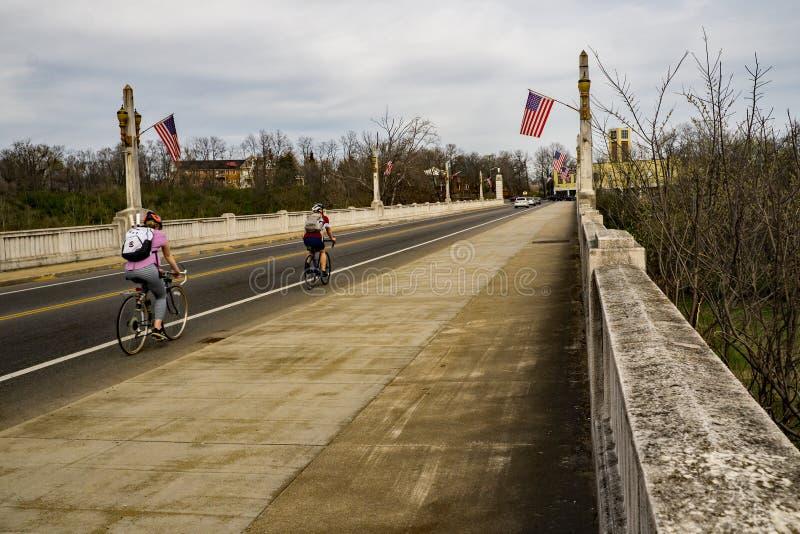 过纪念桥梁,罗阿诺克,弗吉尼亚,美国的两个骑自行车者 库存图片
