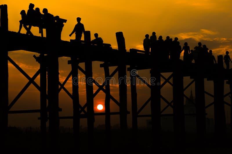 过U有日落的,练马长绳的现出轮廓的人民bein桥梁 免版税图库摄影