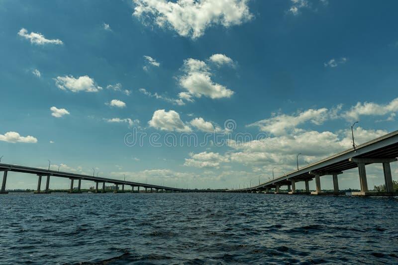 迈尔斯堡风景和都市风景与水和多云蓝天 Caloosahatchee河和桥梁 图库摄影