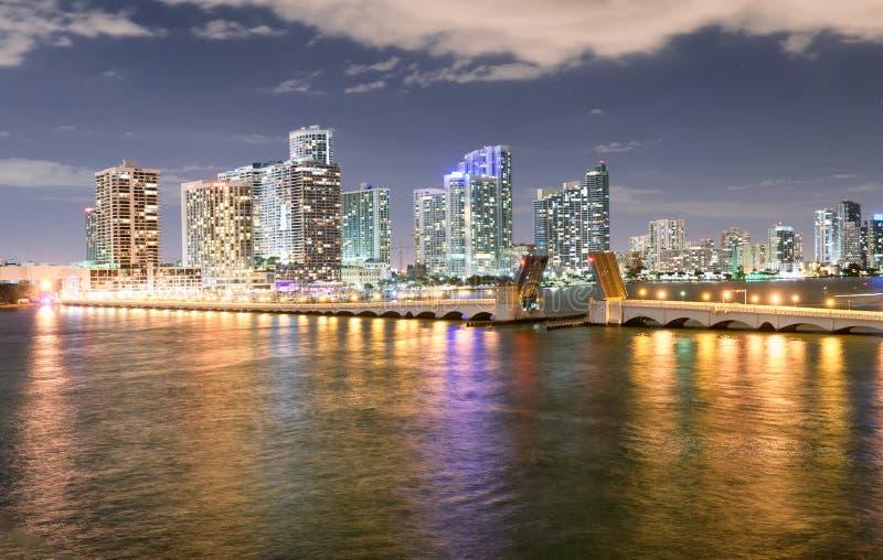 迈阿密从麦克阿瑟堤道的夜地平线 大厦reflectio 免版税库存图片