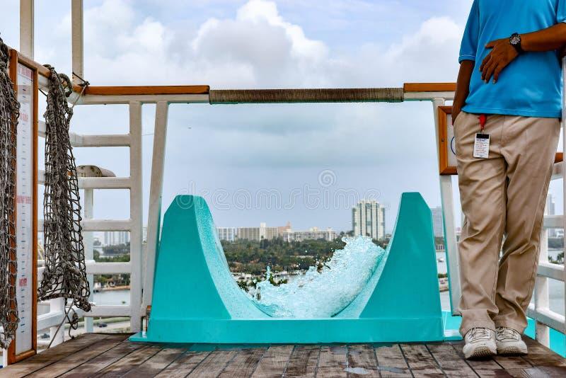 迈阿密,佛罗里达- 2014年3月29日:坚持水滑道的上面的狂欢节自由游轮的成员 图库摄影