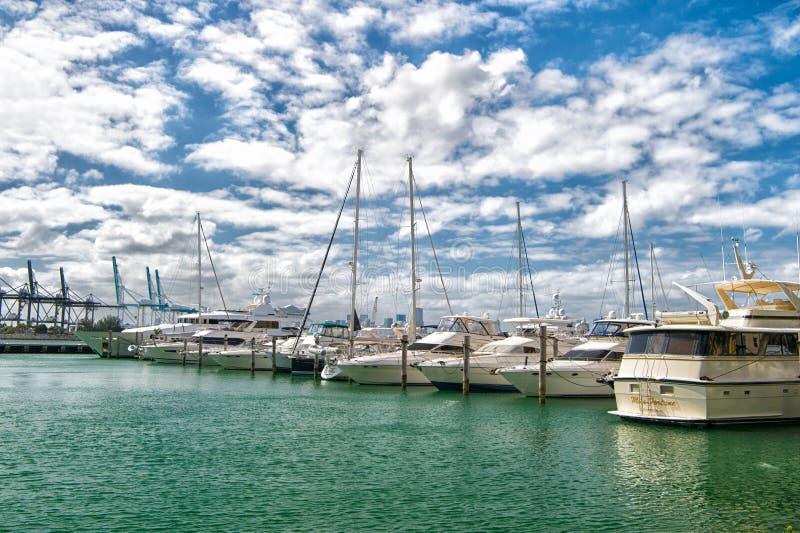 迈阿密,美国- 2016年2月19日:游艇和帆船在海港在多云蓝天 乘快艇和航行 在小船的豪华旅行 库存图片