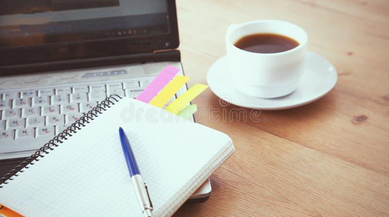 运作与膝上型计算机、笔记薄和咖啡的办公室桌面看法 免版税库存照片