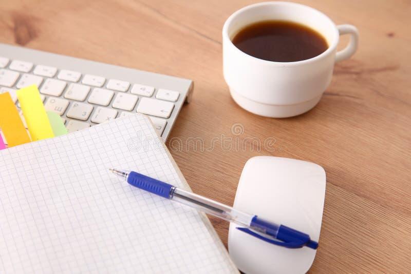 运作与膝上型计算机、笔记薄和咖啡的办公室桌面看法 库存照片