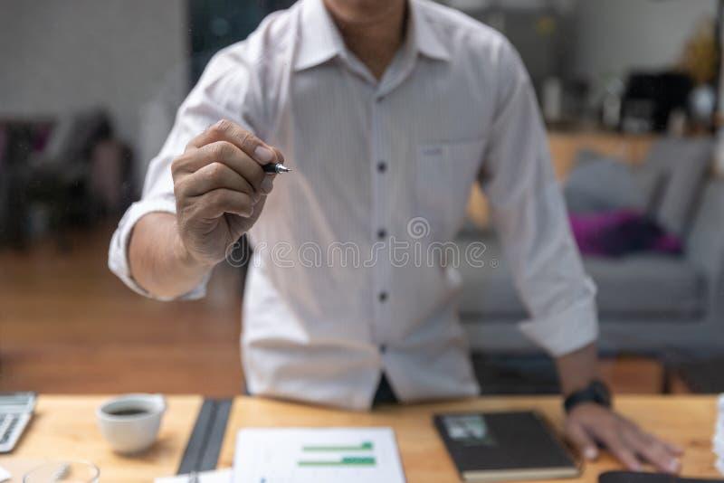 运作办公室的企业和财务的概念,写投资经营计划的商人在窗口 图库摄影