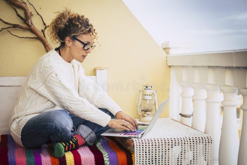 运作和键入在室外的大阳台的膝上型计算机笔记本的美好的白种人女性中年 工作自由在办公室外面 库存照片