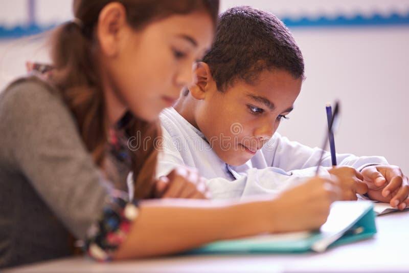 运作在书桌的两个小学学生在教训期间 库存照片