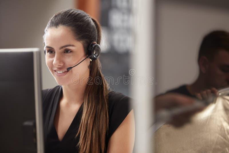 运作在书桌的女性客服代理在电话中心 免版税图库摄影