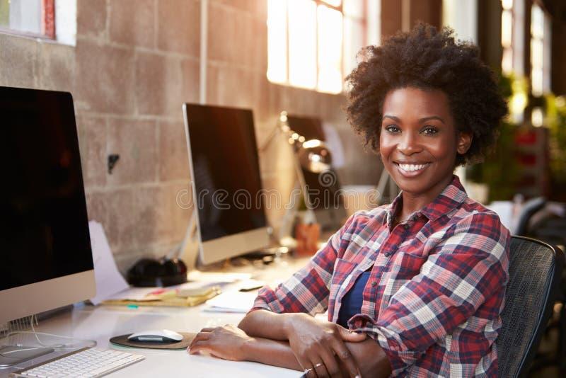 运作在书桌的女性设计师画象在现代办公室 免版税库存照片