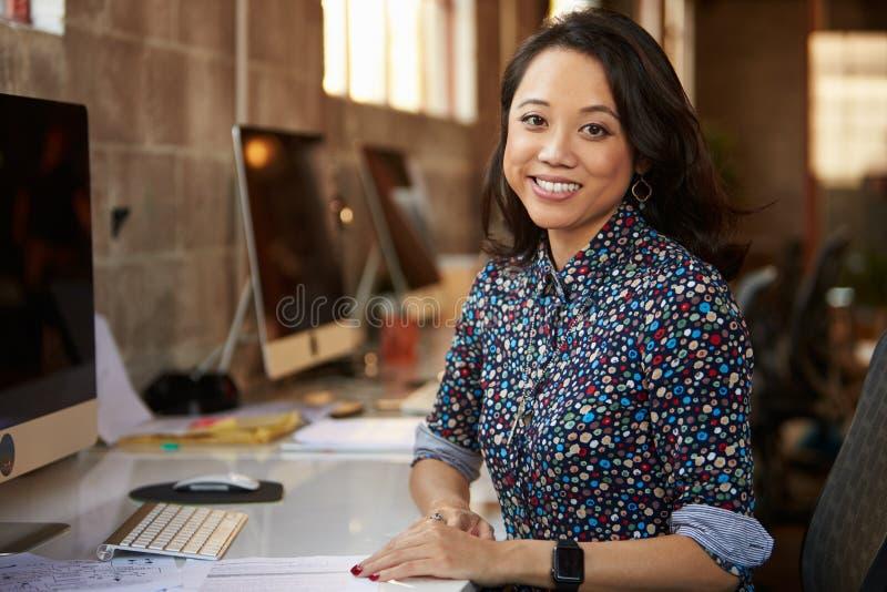 运作在书桌的女性设计师画象在现代办公室 免版税图库摄影