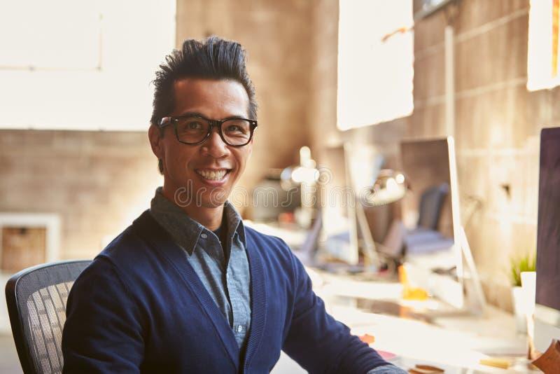运作在书桌的男性设计师画象在现代办公室 免版税库存照片